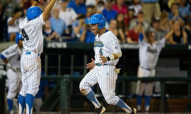 UCLA's Brian Carroll (24), left, and Eric Filia (4) celebrate after scoring off a double hit by Pat Valaika (10) against North Carolina in the bottom of the seventh inning in Game 12 of the College World Series at TD Ameritrade Park in Omaha, Neb., Friday, June 21, 2013. (AP Photo/The Omaha World-Herald/Matt Miller) MAGAZINES OUT; ALL LOCAL TV OUT