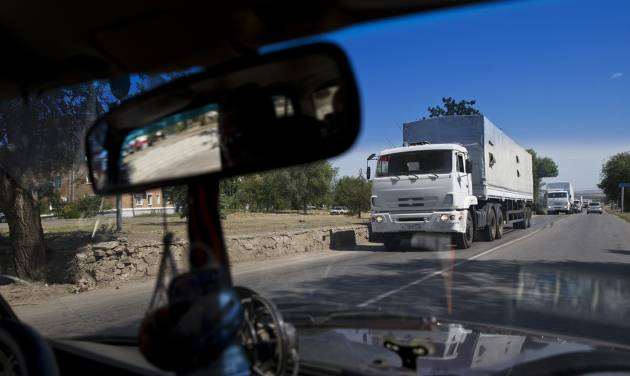 Trucks move towards a border control point with Ukraine in the Russian town of Donetsk, Rostov-on-Don region, Russia, Friday, Aug. 22, 2014. The first trucks of the Russian aid convoy crossed the Ukrainian inspection zone Friday morning. (AP Photo/Pavel Golovkin)