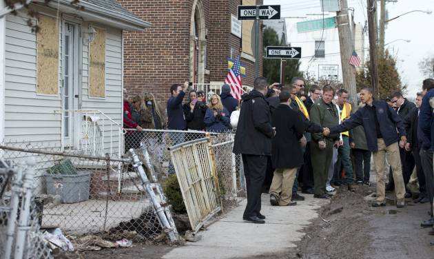 President Barack Obama visits with people on Cedar Grove Avenue, a street significantly impacted by Superstorm Sandy, on the Staten Island borough of New York, Thursday, Nov. 15, 2012. (AP Photo/Carolyn Kaster)