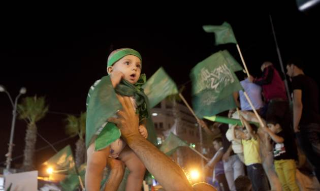 A Palestinian Hamas supporter holds up a little girl wearing green flags as people gather in the streets during celebrations for the cease-fire between Palestinians and Israelis, in the West bank city of Ramallah, Tuesday, Aug. 26, 2014.  Israel and Hamas agreed Tuesday to an open-ended cease-fire, halting a seven-week war that killed more than 2,200 people, the vast majority Palestinians, left tens of thousands in Gaza homeless and devastated entire neighborhoods in the blockaded territory. (AP Photo/Majdi Mohammed)