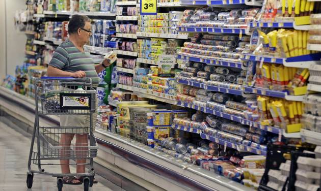 In this June 17, 2014 photo, a shopper looks at an item in the dairy section of a Kroger grocery store in Richardson, Texas. The Conference Board releases the Consumer Confidence Index for June on Tuesday, June 24, 2014. (AP Photo/LM Otero)