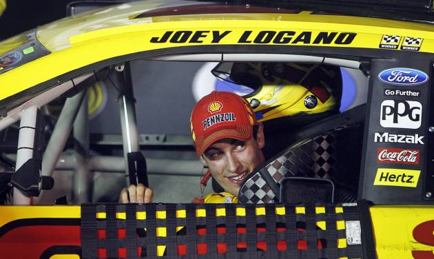 Driver Joey Logano peeks out his window as he pulls into victory lane after winning a NASCAR Sprint Cup Series auto race at Bristol Motor Speedway on Saturday, Aug. 23, 2014, in Bristol, Tenn. (AP Photo/Wade Payne)
