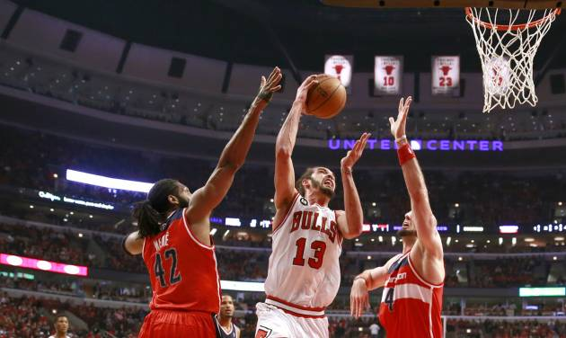 Chicago Bulls center Joakim Noah (13) shoots between Washington Wizards forward Nene Hilario (42) and Marcin Gortat during the first half of Game 2 in an opening-round NBA basketball playoff series Tuesday, April 22, 2014, in Chicago. (AP Photo/Charles Rex Arbogast)
