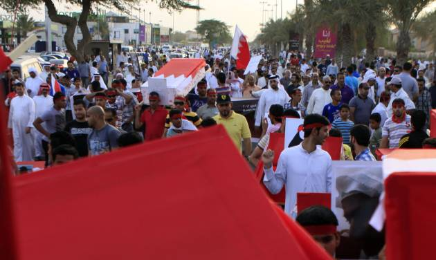"Anti-government protesters carry symbolic coffins draped in Bahraini flags Friday, May 4, 2012, during a mass march in Barbar, Bahrain, west of the capital of Manama, in memory of those who have died in the past year's pro-democracy uprising. Protesters called for political prisoners to be freed and the opposition parties that organized the march said in a statement that newly approved changes to the nation's constitution are merely cosmetic and ""prove an ignorant mentality toward reforms and change."" (AP Photo/Hasan Jamali)"