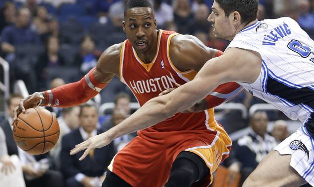 Houston Rockets' Dwight Howard, left, makes a move to get around Orlando Magic's Nikola Vucevic during the first half of an NBA basketball game in Orlando, Fla., Wednesday, March 5, 2014. (AP Photo/John Raoux)