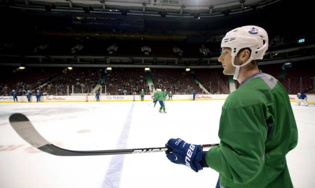 Vancouver Canucks' Cam Barker watches during NHL hockey training camp at Rogers Arena in Vancouver, British Columbia, Monday, Jan., 14, 2013. (AP Photo/The Canadian Press, Jonathan Hayward)