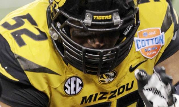 "In this Jan. 3, 2014 photo, Missouri defensive lineman Michael Sam (52) warms up, as he wears an ""MU Pride"" bracelet made by Triangle Coalition, a student organization for lesbian, gay, bisexual and transgender people, before the Cotton Bowl NCAA college football game against Oklahoma State, in Arlington, Texas. Michael Sam hopes his ability is all that matters, not his sexual orientation. Missouri's All-America defensive end came out to the entire country Sunday night, Feb. 9, 2014, and could become the first openly gay player in America's most popular sport. (AP Photo/Tim Sharp)"