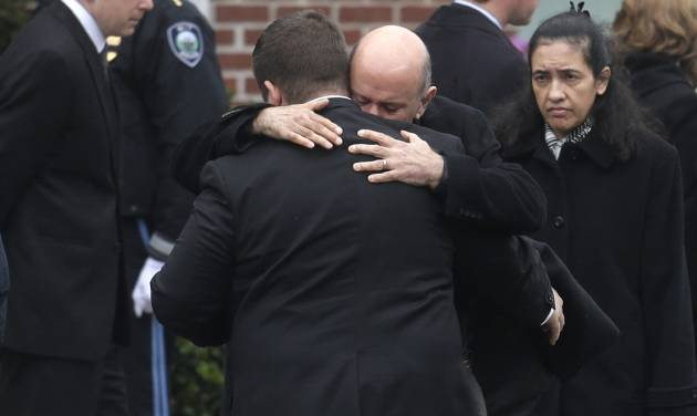 Mourners hug as they depart St. Patrick's Church in Stoneham, Mass., following a funeral Mass for Massachusetts Institute of Technology police officer Sean Collier, Tuesday, April 23, 2013. Collier was fatally shot on the MIT campus Thursday, April 18, 2013. Authorities allege that the Boston Marathon bombing suspects were responsible. (AP Photo/Steven Senne)