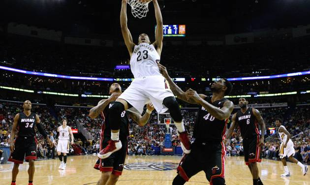 New Orleans Pelicans forward Anthony Davis (23) dunks the ball over Miami Heat defenders Udonis Haslem, right, and Michael Beasley, left, during the first half of an NBA basketball game in New Orleans, Saturday, March 22, 2014. (AP Photo/Jonathan Bachman)
