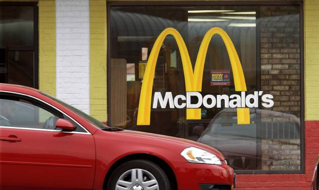 """FILE - This Oct. 17, 2011 file photo, cars move through the drive-thru window at a McDonald's in Springfield, Ill. McDonald's Corp. on Tuesday, July 29, 2014 said it has been notified by the National Labor Relations Board that it can be named a """"joint employer"""" for workers in its franchisee-owned restaurants. (AP Photo/Seth Perlman, File)"""