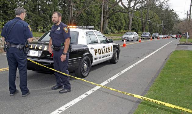 In this March 24, 2012, photo, Norwalk, Conn., police stand at the scene of an accident on New Canaan Avenue where Kenneth Dorsey, 43, of Norwalk was fatally struck by an SUV while he was jogging. A 16-year-old girl from New Canaan, Conn., who police say was driving the SUV, turned herself in May 12, 2012, after learning there was a warrant out for her arrest on charges of negligent homicide with a motor vehicle. (AP Photo/The Hour, Danielle Robinson) MANDATORY CREDIT