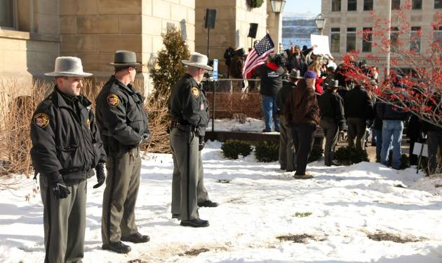 "Jefferson Co. sheriff's deputies stand nearby during the  protest at the Jefferson County Courthouse in Steubenville, Ohio, Saturday, Jan. 5, 2013. Authorities investigating rape accusations against two high school football players in eastern Ohio launched a website Saturday as interest in the case balloons, an extraordinary step designed to combat the misperception ""that the football team runs the city,"" the city manager said. (AP Photo/The Plain Dealer, Thomas Ondrey) MANDATORY CREDIT; NO SALES"