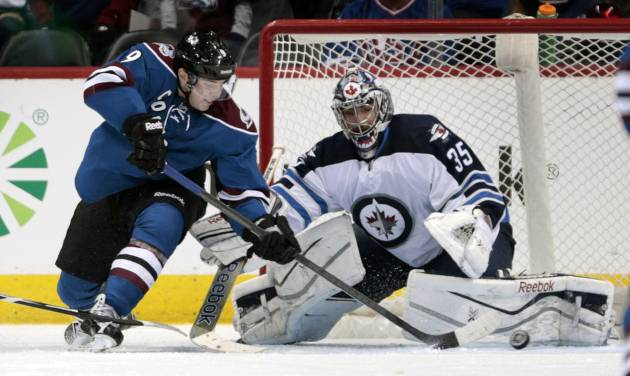 Colorado Avalanche center Matt Duchene (9) reaches for the puck in front of Winnipeg Jets goalie Al Montoya (35) during the second period of an NHL hockey game in Denver on Sunday, Dec. 29, 2013. (AP Photo/Joe Mahoney)