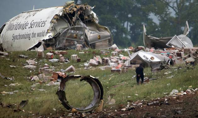 FILE - In this Aug. 14, 2013, file photo, a investigator looks through debris of a UPS A300 cargo plane after it crashed on approach at Birmingham-Shuttlesworth International Airport in Birmingham, Ala. Federal investigators are looking at pilot fatigue, among other issues, as a possible factor in the fatal predawn crash of a UPS cargo jet. The National Transportation Safety Board scheduled a hearing for Feb. 20, 2014, on the accident, which killed both pilots. (AP Photo/Hal Yeager, File)