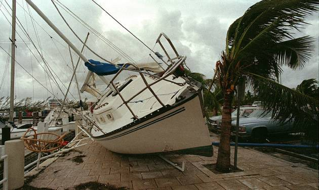 FILE - In this Aug. 24, 1992 file photo, a sailboat sits on a sidewalk at Dinner Key in Miami after it was washed ashore by Hurricane Andrew. Global warming is rapidly turning America into a stormy and dangerous place, with rising seas and disasters upending lives from flood-stricken Florida to the wildfire-ravaged West, the National Climate Assessment concluded Tuesday, May 6, 2014.  (AP Photo/Terry Renna, File)