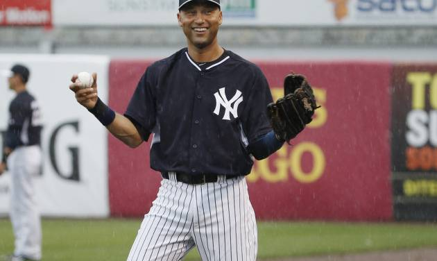 New York Yankees Derek Jeter laughs as he throws in the rain before a spring exhibition baseball game against the Miami Marlins was canceled due to the weather in Tampa, Fla., Saturday, March 29, 2014. (AP Photo/Kathy Willens)