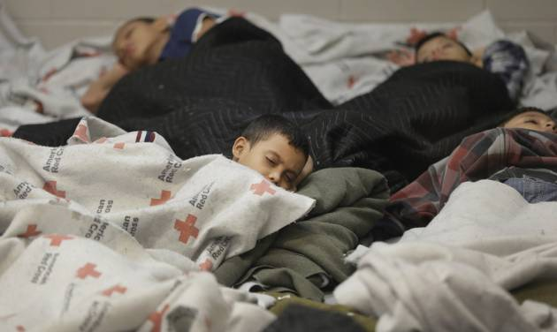 FILE - In this June 18, 2014, file photo, detainees sleep in a holding cell at a U.S. Customs and Border Protection, processing facility in Brownsville,Texas. Many of the immigrants recently flooding the nation's southern border say they're fleeing violent gangs in Central America. These gangs were a byproduct of U.S. immigration and Cold War policies, specifically growing from the increase in deportations in the 1990s. With weak dysfunctional governments at home, U.S. street gang culture easily took hold and flourished in these countries. (AP Photo/Eric Gay, Pool, File)