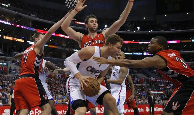 Los Angeles Clippers' Blake Griffin, center, is defended by Toronto Raptors' Jonas Valanciunas, left, of Lithuania, Kyle Lowry, right, and Andrea Bargnani, of Italy, in the first half of an NBA basketball game in Los Angeles, Sunday, Dec. 9, 2012. (AP Photo/Jae C. Hong)