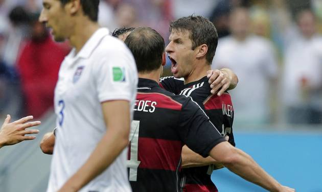 Germany's Thomas Mueller, right, celebrates scoring the opening goal as United States' Omar Gonzalez, left, walks away during the group G World Cup soccer match between the USA and Germany at the Arena Pernambuco in Recife, Brazil, Thursday, June 26, 2014. (AP Photo/Matthias Schrader)