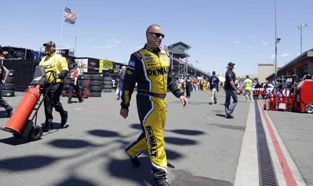 Marcos Ambrose walks to his car before the start of practice for the NASCAR Sprint Cup Series auto race Friday, June 20, 2014, in Sonoma, Calif. Ambrose wants nothing more than to break Hendrick Motorsports' four-race winning streak. His best shot comes Sunday on the road course at Sonoma Raceway, where a win could earn the Australian his first berth in the Chase for the Sprint Cup championship. (AP Photo/Eric Risberg)