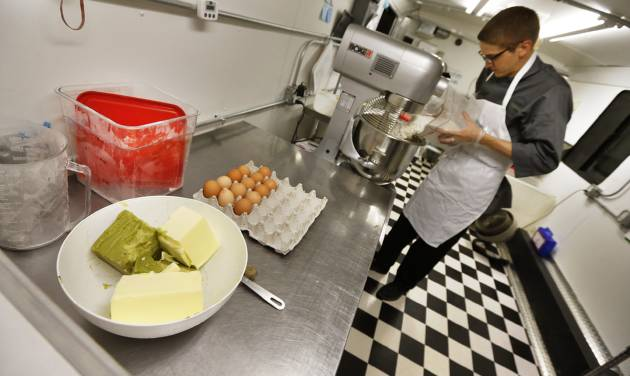 """In this June 19, 2014 photo, chef Alex Tretter prepares a batter for peanut butter and jelly cups, with green cannabis-infused """"canna butter"""" in a bowl at left, at Sweet Grass Kitchen, a well-established gourmet marijuana edibles bakery which sells its confections to retail outlets, in Denver. Sweet Grass Kitchen, like other cannabis food producers in the state, is held to rigorous health inspection standards, and has received praise from inspectors, according to owner Julie Berliner. (AP Photo/Brennan Linsley)"""