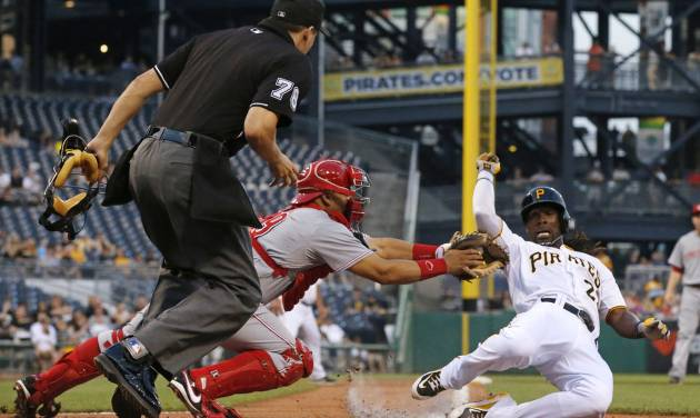 Cincinnati Reds catcher Brayan Pena, center, tags out Pittsburgh Pirates' Andrew McCutchen, right, in front of umpire Alan Haman to end the third inning of a baseball game in Pittsburgh Tuesday, June 17, 2014. McCutchen was attempting to score from third on a fly out to center field by Pirates Pedro Alvarez. (AP Photo/Gene J. Puskar)