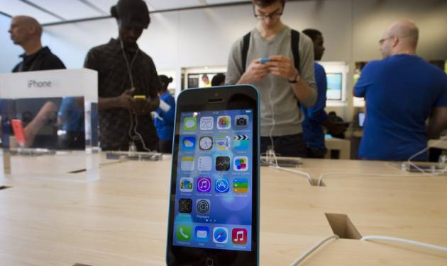 Customers check out the latest versions of the iPhone that went on sale Friday, Sept.  20, 2013 in Montreal. Friday is the first time Apple is releasing two different iPhone models at once. (AP Photo/The Canadian Press, Ryan Remiorz)