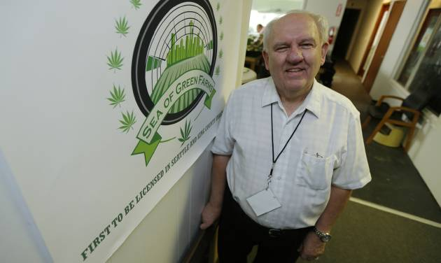 In this June 25, 2014 photo, Bob Leeds, who retired from banking and social-services work to become a partner at Sea of Green Farms, a licensed pot-grower in Seattle, stands next to his company's logo. Sea of Green is licensed to grow some of the first pot that will be legally sold for recreational use in Washington state starting in July. (AP Photo/Ted S. Warren)