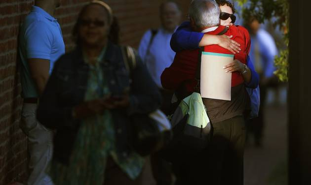 A woman hugs a man before entering the Washington Navy Yard as employees return to work, Thursday, Sept. 19, 2013. The Washington Navy Yard returned to nearly normal operations three days after it was the scene of a mass shooting in which a gunman killed 12 people. (AP Photo/Charles Dharapak)