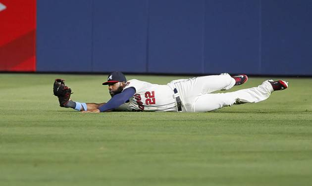 Atlanta Braves right fielder Jason Heyward makes a diving catch of a ball hit by Los Angeles Angels Mike Trout in the fourth inning inning of an interleague baseball game Sunday, June 15, 2014, in Atlanta. (AP Photo/Todd Kirkland)