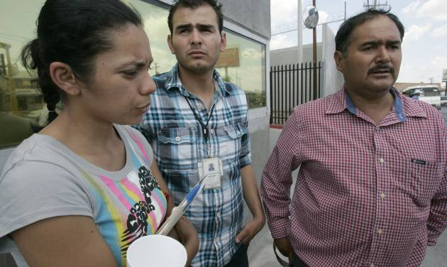 Family members, from left, Myrna Ramirez, Cesar De La Fuente and Homero De La Fuente,47, father and brother of Manuel Homero De La Fuente, 19, a Pemex worker who is still missing after the gas explosion on Tuesday, wait to hear word of their loved one at the PGR facility in Reynosa, Mexico, Wednesday, Sept .19, 2012. (AP Photo/The Monitor, Delcia Lopez)