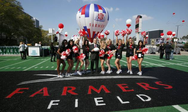 "FILE - In this Feb. 1, 2011, file photo, Paul Patsis, president of Market Management for Farmers Insurance, center, poses with Los Angeles Kings cheerleaders during a ceremony naming a new proposed NFL football stadium in Los Angeles, that would be called Farmers Field under a 30-year naming-rights deal between developer AEG and Farmers Insurance Exchange. Denver-based Anschutz Co. said Tuesday, Sept. 18, 2012, that it was ""commencing a process"" to sell subsidiary Anschutz Entertainment Group, and the announcement left especially big questions about AEG's central role in courting the NFL's return to Los Angeles with Farmers Field, a planned downtown stadium going through late-round approvals with the city. (AP Photo/Nick Ut, File)"