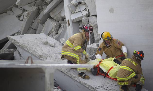 Fire Rescue officials work to remove a victim from the collapsed parking garage at the Miami Dade College West campus in Doral, Fla. Tuesday, Oct. 10, 2012 . A section of a parking garage under construction at a community college collapsed killing one worker and trapping two others in the rubble, officials said. At least 10 other workers were hurt when the roof of the five-story concrete garage fell, creating a pancake-style collapse on the campus of Miami-Dade College, officials said. (AP Photo/J Pat Carter)