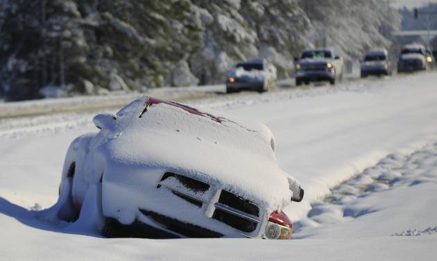 A vehicle abandoned by its driver lays buried in snow along the median of Mauamelle Blvd. in Little Rock, Ark. Wednesday morning, Dec. 26, 2012.  A historic Christmas night winter storm dropped upwards of a foot of snow on parts of Arkansas, shutting down workplaces, downing trees and power lines and turning travel treacherous. (AP Photo/The Arkansas Democrat-Gazette, Benjamin Krain)  ARKANSAS TIMES OUT; ARKANSAS BUSINESS OUT