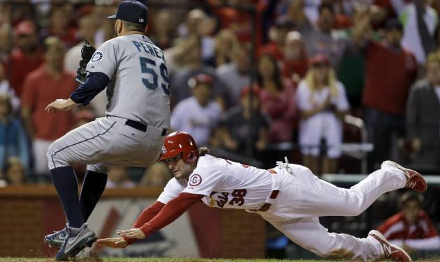 St. Louis Cardinals' Pete Kozma, right, scores the game-winning run on a passed ball as Seattle Mariners relief pitcher Oliver Perez covers home during the 10th inning of a baseball game Friday, Sept. 13, 2013, in St. Louis. The Cardinals won 2-1. (AP Photo/Jeff Roberson)