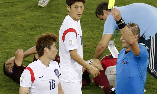 Referee Nestor Pitana from Argentina, right, books South Korea's Ki Sung-yueng (16) after a foul during the group H World Cup soccer match between Russia and South Korea at the Arena Pantanal in Cuiaba, Brazil, Tuesday, June 17, 2014. (AP Photo/Thanassis Stavrakis)