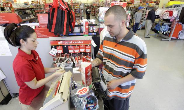 FILE - In this file photo taken Dec. 14, 2010, Family Dollar employee Pamela Ramos, left, assists John Conner with a purchase at a store in Waco, Texas. Family Dollar on Thursday, April 10, 2014 said it will be cutting jobs and closing about 370 underperforming stores as it looks for ways to improve its financial performance. It says it will also cut prices on about 1,000 basic items. (AP Photo/Tony Gutierrezfile, File)