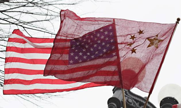 FILE - In this Jan. 17, 2011 file photo, American and Chinese flags fly along Pennsylvania Avenue in front of the White House in Washington. The Justice Department's indictment last week of five Chinese military officials charged them with trying to pilfer confidential information from American companies. But even some of the alleged U.S. corporate victims of the hackers have little incentive to cheer any trade rupture with China. (AP Photo/Carolyn Kaster, File)