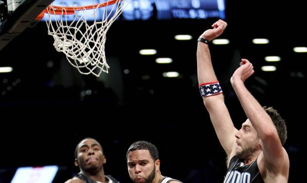 Brooklyn Nets' Deron Williams, center, passes the ball around Orlando Magic's Josh McRoberts, right, and Moe Harkless during the first half of an NBA basketball game in New York, Sunday, Nov. 11, 2012. (AP Photo/Seth Wenig)
