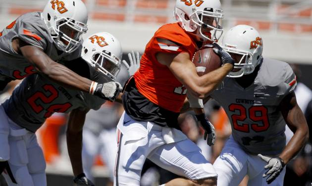 OKLAHOMA STATE UNIVERSITY / OSU / COLLEGE FOOTBALL: OSU's Charlie Moore runs past Jimmy Bean, left, Miketavius Jones, and Cameron Gravelle, right, on his way to a touchdown during Oklahoma State's spring football game at Boone Pickens Stadium in Stillwater, Okla., Saturday, April 21, 2012. Photo by Bryan Terry, The Oklahoman