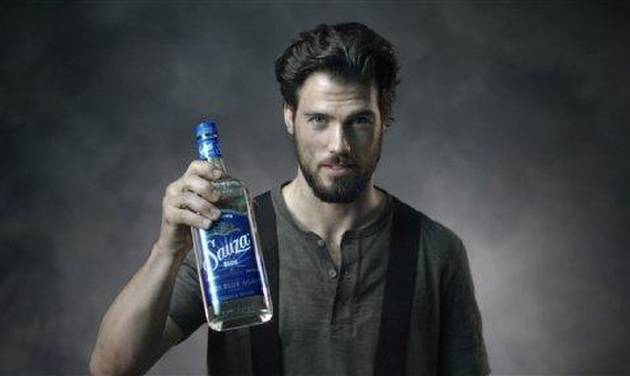 "This image from video released by Sauza shows a fireman holding a bottle of Sauza Tequila for a video directed by Matt Lenski for the ""Make it with a Fireman"" campaign. The ad, launched in April, reflects a shift in spirits marketing as some producers look beyond traditional male-oriented campaigns. (AP Photo/Sauza)"
