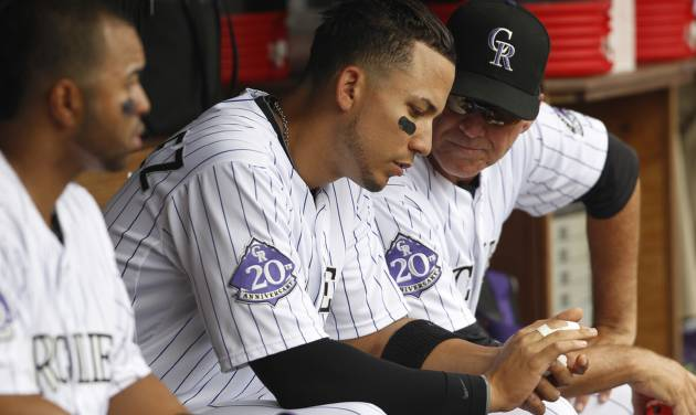 Colorado Rockies left fielder Carlos Gonzalez, center, shows his fingers to bench coach Tom Runnells, right, while facing the Miami Marlins in the third inning of a baseball game in Denver, Thursday, July 25, 2013. Gonzalezplayed in the fourth inning but was removed from the game upon returning to the dugout. (AP Photo/David Zalubowski)