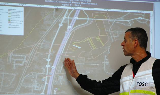 Federal on-scene coordinator Nick Brescia use a projection of a map as he talks to reporters on Thursday, April 11, 2013, about efforts to clean up after last month's oil spill in Mayflower, Ark. Some people whose homes were evacuated when an oil pipeline ruptured in central Arkansas could go home as early as Thursday, officials said.  (AP Photo/Jeannie Nuss)