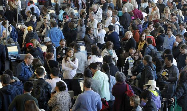 Passengers gather at the American Airlines check-in for flights at Los Angeles International Airport on Tuesday, April 16, 2013. Computer problems forced American Airlines to ground flights across the country Tuesday after the airline was unable to check passengers in and book passengers. (AP Photo/Nick Ut)