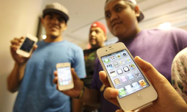 FILE - In this Oct. 14, 2011 file photo, the Leon Guerrero family, on vacation from Dallas, show off their new Apple iPhone 4S phones they purchased at a Sprint store in San Francisco. Apple said Monday, Oct. 17, 2011, it sold more than 4 million units of the new iPhone model in three days. It's selling more than twice as fast as the previous model did when it launched last year. (AP Photo/Eric Risberg, File)