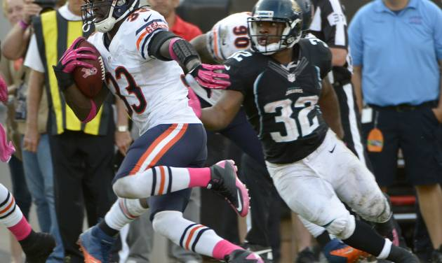 Chicago Bears cornerback Charles Tillman (33) runs past Jacksonville Jaguars running back Maurice Jones-Drew (32) after intercepting a pass for a 36-yard touchdown during the second half of an NFL football game, Sunday, Oct. 7, 2012, in Jacksonville, Fla. (AP Photo/Phelan M. Ebenhack)