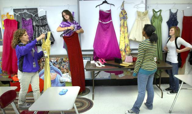 In this photo taken Oct. 2, 2012 in Bloomington, Ill., from left, English teacher and senior advisor Gloria McElwain, helps her daughter, Ginny McElwain, 17, a senior, Kiara Cross, 16, and Alexandra Furoman, 16, both juniors, as they set up prom dresses for Bloomington High School's House of Style. The House of Style started four years ago when advisor McElwain, urged a student to go to the prom who said she couldn't afford a dress. McElwain was not deterred by the students predicament and got the girl a dress and she went to the dance. Since then McElwain and various volunteers have given away 370 dresses to BHS students for homecoming and prom dances, even weddings. (AP Photo/The Pantagraph, David Proeber)