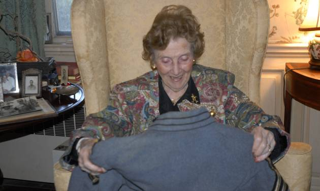 In this photo taken Wednesday, Nov. 28, 2012, Teresa deGavre smiles as she looks at her late husband's West Point uniform jacket at her home near Onancock, Va. The Chester B. deGavre's jacket was discovered on a beach in New Jersey after Superstorm Sandy by Donna Gugger of Holland, Pa. who returned it Wednesday. (AP Photo/Eastern Shore News, Malissa Watterson) NO SALES