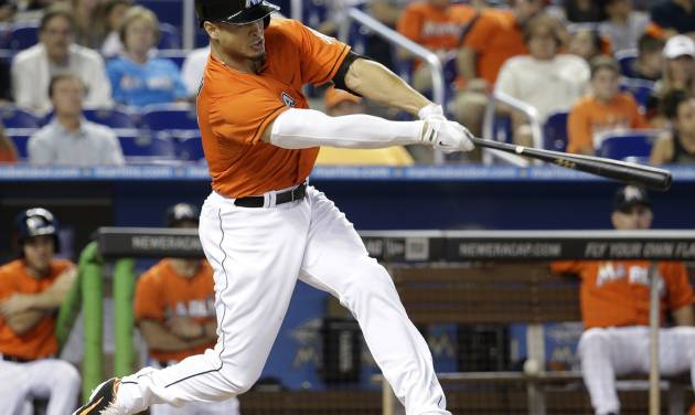 Miami Marlins' Giancarlo Stanton hits a three-run home run in the first inning off Arizona Diamondbacks starting pitcher Josh Collmenter during a baseball game, Sunday, Aug.17, 2014, in Miami. (AP Photo/Lynne Sladky)