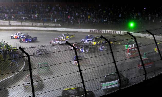 Drivers head through a turn on the opening lap of the NASCAR Truck Series auto race Wednesday, July 24, 2013, on the dirt at Eldora Speedway in Rossburg, Ohio. (AP Photo/Dayton Daily News, Greg Lynch) LOCAL PRINT OUT AND LOCAL TV OUT (WKEF, WRGT, WDTN)